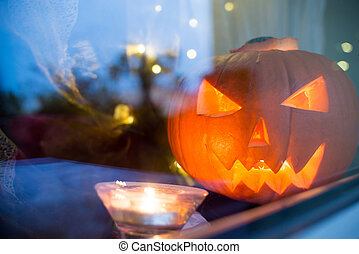 bright Halloween pupkin symbol behind the home window with light reflectons