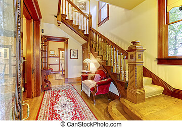 Bright hallway with colourful rug, nice red sofa, wooden staircase and beige carpet covered steps