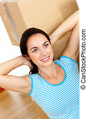 Bright hispanic woman relaxing at the middle of boxes on the floor in her new house