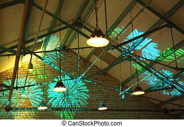 bright illumination. green and blue abstract shapes on brick wall