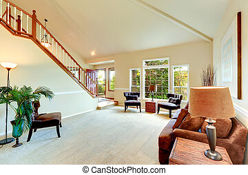 Bright ivory living room with high vaulted ceiling and french window and staircase. Room furnished with brown sofa, antique chairs and derocated with wicker vase with dry branches and palm tree