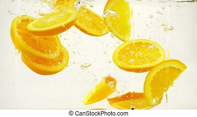 Bright juicy orange slices with a splash and bubbles falling into water, slow motion close-up