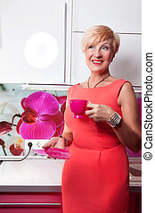 Bright kitchen and happy middle aged woman with red mug of coffee