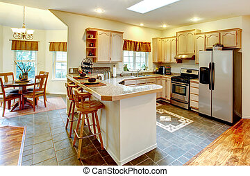 Bright kitchen room with maple storage cabinets and stainless steel appliances. View of dining area
