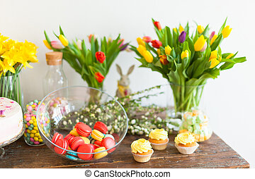 Bright macaroons and cupcakes on a wooden table