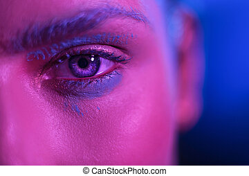 Bright makeup stylish girl model with blue eyes on a blue background.