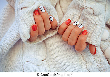 Bright manicure in light on a knitted background