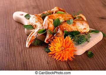 Bright marigold bloom in front of chopping board with marinated wings