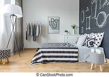 Bright minimalist bedroom with blackboard wall with mirror drawings