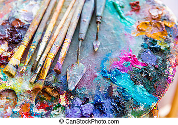 Bright mixed color paints on art palette with paintbrushes -...