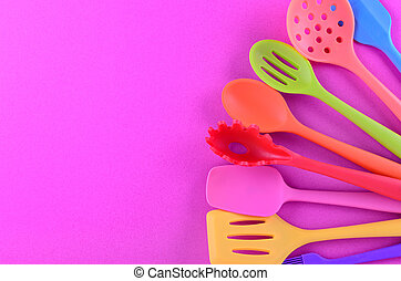 bright multi colored kitchen utensils on purple background with copy space