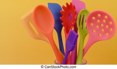 bright multi colored kitchen utensils on yellow background -...