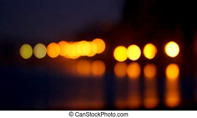 Bright night lights are reflected in sea water against the background of multi-storey buildings. bokeh
