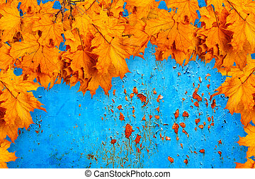 Bright orange autumn leaves on the background of rusty metal wal