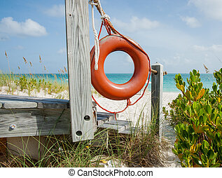Bright orange life bouy hanging on side of beach access on ...