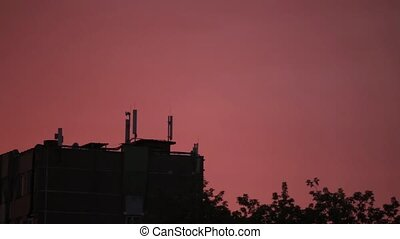 Bright orange-red sun rises over building, electro transmission lines, Telecommunication antennas and trees.
