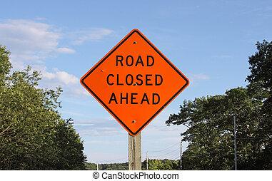 Bright orange road closed ahead sign