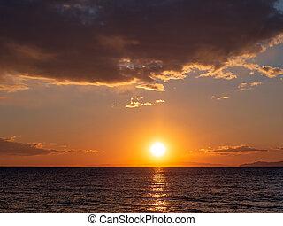 Bright orange sunset over the sea - islands on the horizon