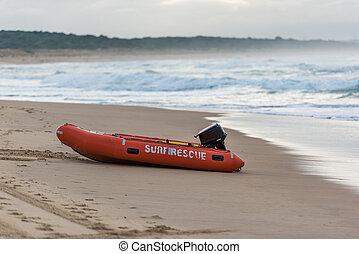 Bright orange surf saver boat on sandy beach shore....