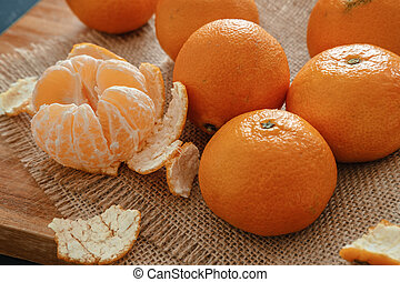 Bright orange tangerines (clementines) on a wooden background with burlap