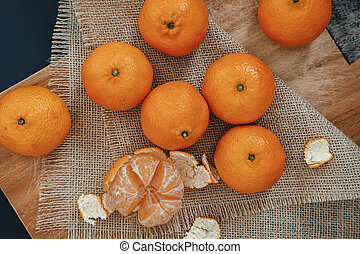 Bright orange tangerines (clementines) on a wooden background with burlap overhead