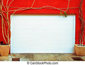 Metal garage door framed by leafless plants in France