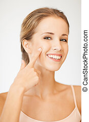 beautiful woman pointing to cheek - bright picture of...