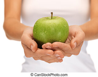 female hands with green apple