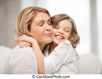 mother and daughter - bright picture of hugging mother and...