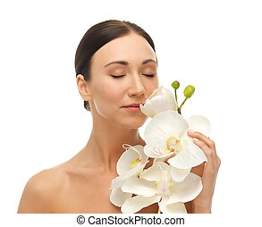 woman smelling white orchid flower