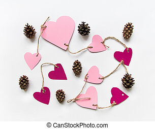 Bright pink paper hearts connected with a rope for Valentine's day. Flat lay on white background