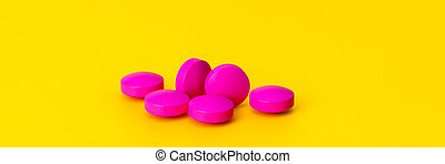 Bright pink pills scattered on a yellow background.