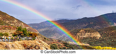 Bright rainbow on a rainy day in southern California; hills and valleys covered in chaparral; Pyramid Lake, Los Angeles County, California