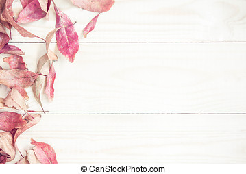 Bright red autumn leaves on the wooden background.