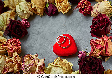 bright red heart with wedding rings on the gray concrete background