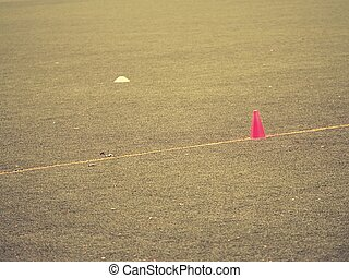 Bright red plastic cone on painted white line of soccer field. Football green playground