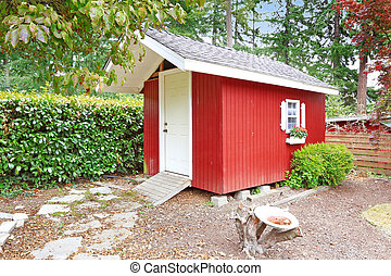 Bright red shed on backyard area - Bright red wooden shed on...