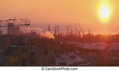 Bright red sunset. Industrial shot. Many hoisting cranes...