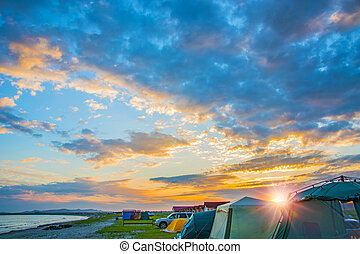 bright red sunset over the beach, there are a number of tents. tourist camp. blue sky