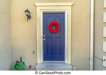Bright red wreath on the blue front door of a home with outdoor wall lamp