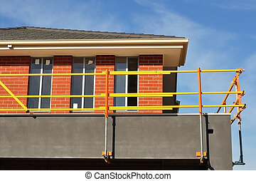 Yellow scaffolds on unfinished house