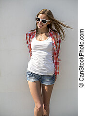 Bright sexy, beautiful young girl, wearing glasses posing in front of a white wall
