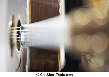 Bright side view of an acoustic western guitar with shallow depth of field