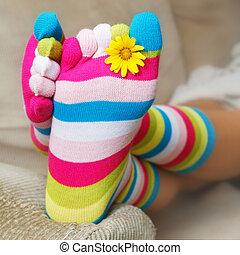 Bright socks and a daisy on the sofa