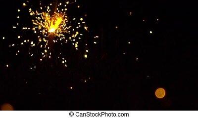Bright sparkler against dark background. Super slow motion...
