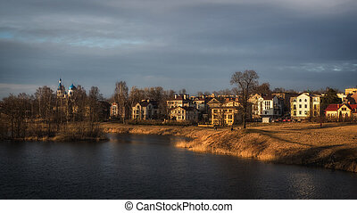 Bright spring landscape with houses near a lake in the evening