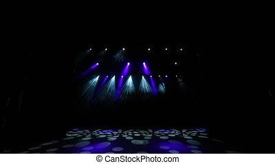 Bright stage lights flashing. Lighting equipment. The lighting designer. Theatrical smoke