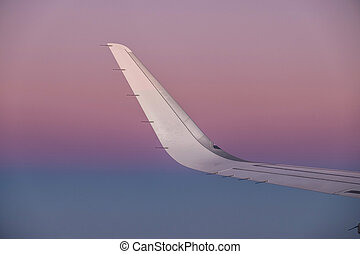 sun at the wing of an aircraft flying in sunrise
