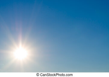 Background image of a bright sun flare in clear blue sky with plenty of copyspace