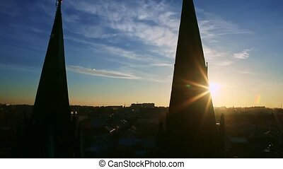 bright sun hiding behind silhouettes of high church spires against blue sky with slowly floating white clouds above old historical town on sunset
